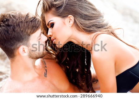 Romantic Young Couple Relaxing On Beach,Young happy woman and her handsome boyfriend laying outdoor in white sand on the beach,after sunset,relaxing on sand at beach and daydreaming date,passion - stock photo