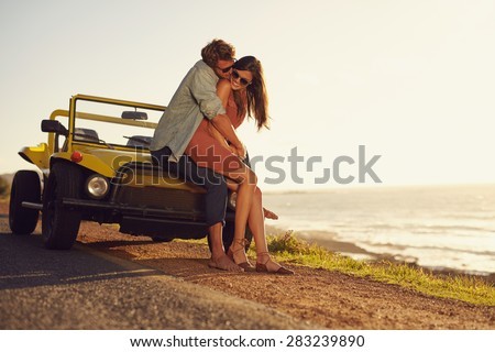 Romantic young couple sharing a special moment while outdoors. Young couple in love on a road trip. Couple embracing each other while sitting on hood of their car in nature. - stock photo