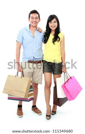 Romantic young couple shopping and holding many shopping bags isolated on white background