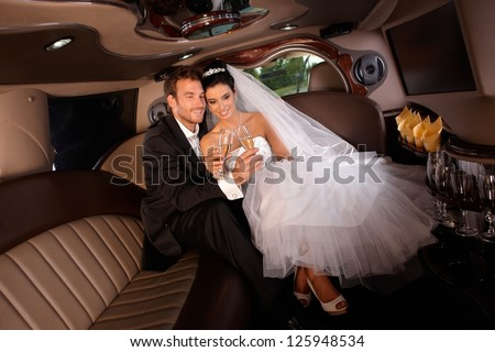 Romantic young couple sitting in limo on wedding-day, clinking glasses. - stock photo