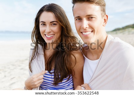 Romantic young couple sitting on the beach looking at camera - stock photo