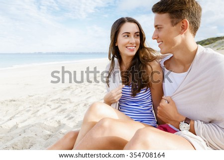 Romantic young couple sitting on the beach looking at each other