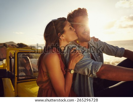 Romantic young couple sitting on the hood of their car while out on a roadtrip. Beautiful young woman kissing her boyfriend looking away smiling, outdoors. - stock photo