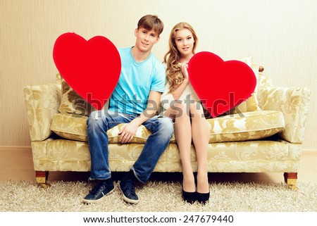 Romantic young couple sitting relaxed on a sofa in the cozy living room of their home. They hold big red hearts. Valentine day.  - stock photo