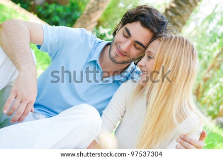 Romantic young couple sitting together in summer park embracing and smiling
