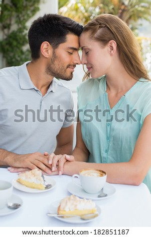 Romantic young couple sitting with eyes closed at the coffee shop