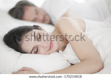 Romantic young couple sleeping in bed - stock photo