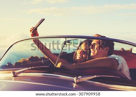 Romantic Young Couple Taking a Selfie in Classic Vintage Sports Car at Sunset - stock photo