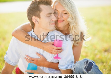 Romantic young couple together outdoors on summer day.Caucasian couple enjoying the beach view.Enjoy time together,lovely couple on the beach,kissing lops,party on beach,tan couple,fashionable outfit - stock photo