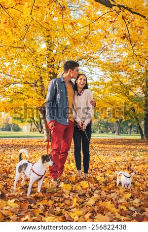 Romantic young couple walking outdoors in autumn park with dogs - stock photo