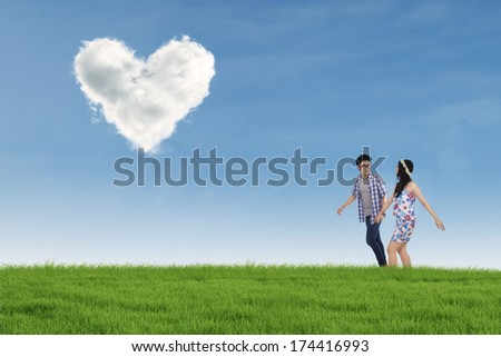 Romantic young couple walking together on the meadow while holding hands with heart shaped cloud