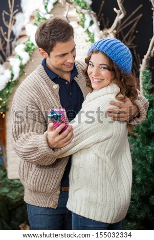 Romantic young couple with gift box while embracing at Christmas store - stock photo