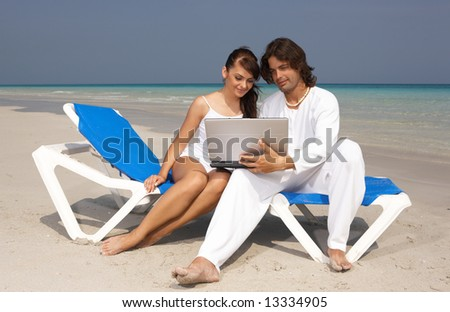 Romantic young couple working on laptop computer at the beach