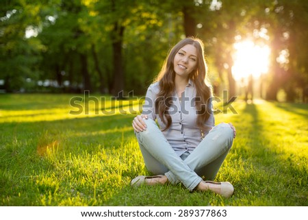 Romantic young girl outdoors enjoying nature Beautiful Model in Casual jeans in light Long healthy Hair  Backlit Warm Color Tones Beauty Sunshine woman Smiling Sunny Summer  Autumn Summertime Glow Sun