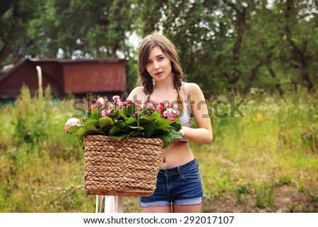 Romantic young girl with her bicycle and flowers in a basket. Summer in the village