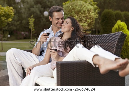 Romantic young holding wine glasses on easy chair in park - stock photo