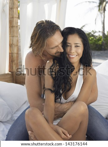 Romantic young man embracing woman on bed in gazebo - stock photo