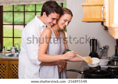 romantic young man hugging girlfriend while she cooks for breakfast - stock photo