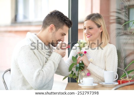 Romantic young man kissing hand of his girlfriend while she smelling a rose - stock photo