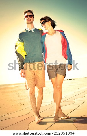 Romantic Young tourist couple standing on a beach at sunset - stock photo