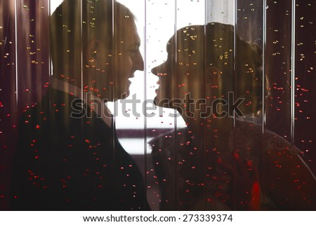 Romantic young wedding couple in love kissing in cafe. Candid view through window glass. - stock photo