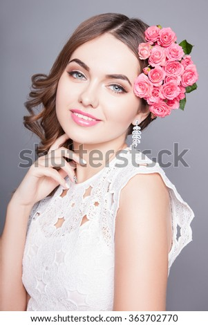 Romantic young woman.An attractive young woman with makeup on his face and flowers in her hair. Portrait of girl with dark hair on a gray background, beautiful makeup on her face - stock photo
