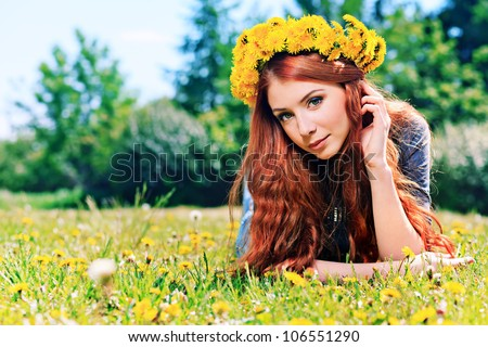 Romantic young woman in a circlet of flowers outdoors. - stock photo