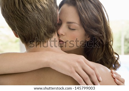 Romantic young woman kissing on man's neck