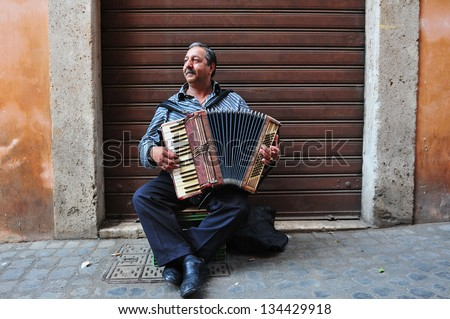 ROME - APRIL 29 2011:Gypsy man playing piano accordion at the Jewish ghetto  in Rome, Italy.The Roman Ghetto was established as a result of Papal bull promulgated by Pope Paul IV in 1555. - stock photo