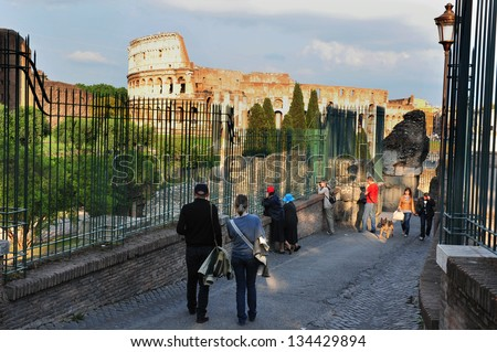 ROME - APRIL 29:Visitors at the Roman Forum and the Colosseum of Rome on April 29 2011 in Rome Italy. Festivals as well as games could last up to 100 days in the Coliseum.  - stock photo
