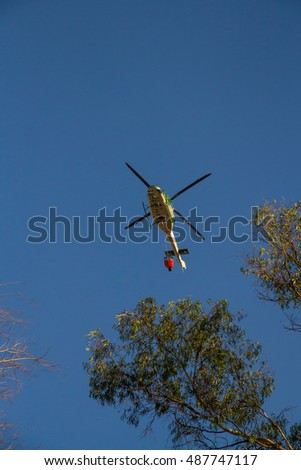 ROME -?? AUGUST 23: Firefighting helicopter carrying bucket containing water from Mediterranean Sea to put out fires on scrubland on August 23, 2016 in Rome.