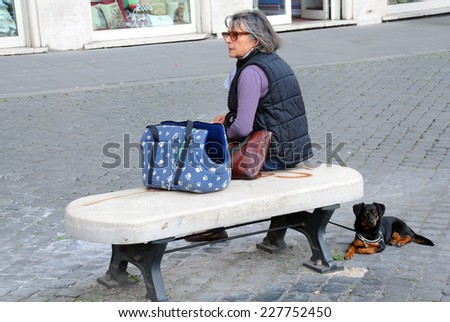 ROME, ITALY -?? APRIL 30, 2014: An unidentified woman sits on the bench and her dog lies next to her
