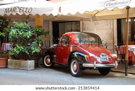 ROME, ITALY - APRIL 11, 2010: Classic car parked outside restaurant in Rome. - stock photo