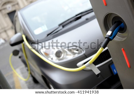 Rome, Italy -  April 11, 2016:  Close up of the power supply plugged into an electric car being charged reducing city pollution. - stock photo