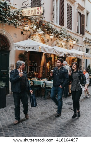 ROME, ITALY - APRIL 21 2016:People enjoying an ice cream while walk in a charming street of Rome, with a restaurant in the background, on April 21, 2016 in Rome, Italy.