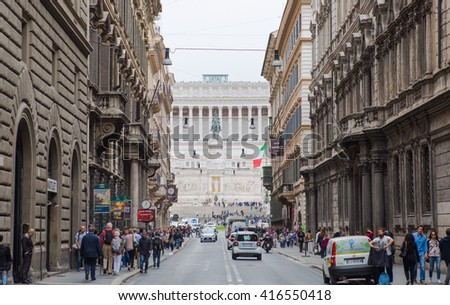 ROME, ITALY - APRIL 8, 2016: Street view with traffic and walking people. Piazza Venezia and  Altar of the Fatherland at the background