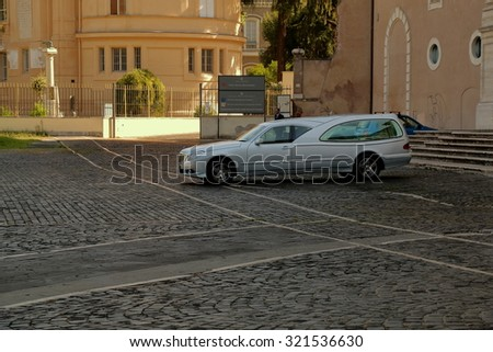 Rome, Italy - August 17, 2015: Hearse near entrance to Basilica di Santa Croce in Gerusalemme in shadow of morning sun - stock photo