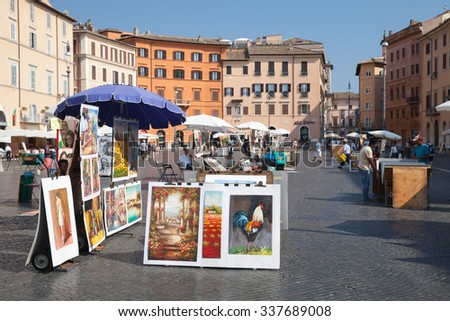 Rome, Italy - August 8, 2015: Piazza Navona, street view with colorful paintings for sale - stock photo