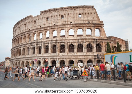 Rome, Italy - August 7, 2015: Tourists walk on the street near Colosseum or Coliseum, also known as the Flavian Amphitheatre of Rome - stock photo