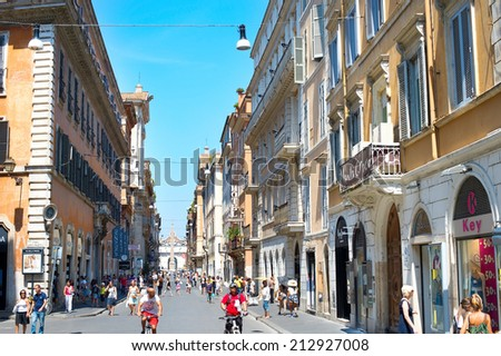 ROME, ITALY - AUGUST 10, 2014: Tourists walking on the Old Town street of Rome. More than 6 million of international tourists visit Rome every year.
