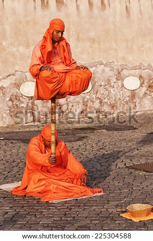ROME, ITALY - JANUARY 08: Indian Fakirs performing levitation trick in Rome on January 08, 2014. In 2011 city council proposed to regulate street performers to remove many of them from Rome. - stock photo