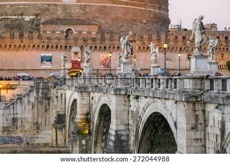 Rome, Italy - January 04, 2015: Landscape of castel sant'angelo in rome along the tiber river, tourist walking on bridge - stock photo