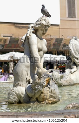 ROME, ITALY - JULY 03, 2010: One Nereid (sea nymph), with a pigeon on its head, statue part of the famous Fontana del Nettuno (Fountain of Neptune) in Piazza Navona, on July 03, 2010. - stock photo