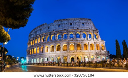 ROME, ITALY - JULY 11, 2015: People in front of illuminated Colosseum at night, panoramic view of famous landmark in the city.
