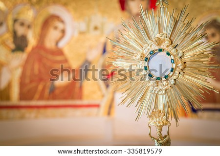 Rome, Italy - June 2015 - Adoration monstrance with the Blessed Sacrament on the altar, artistic edit with dark vignette and copy space for text