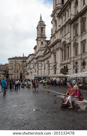 ROME, ITALY - JUNE 18, 2014: Couple of tourists taking a break on a bench in Piazza Navona. Piazza Navona is one of the most famous touristic attractions of Rome. - stock photo