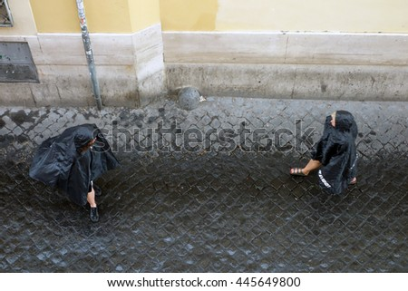 ROME, ITALY - JUNE 20, 2016: People under rain in Lungaretta street, the Trastevere pedestrian area