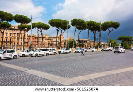 ROME, ITALY - JUNE 10, 2016:  Taxi's lined up waiting for customers along a busy main road, Via dei Fori Imperiali, which leads to the historic Colosseum.