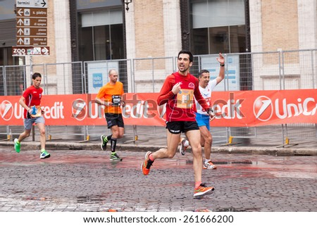 Rome, Italy - March 23, 2014: Participants in the Rome Marathon running through the streets of the city, a street circuit of 40 km. - stock photo