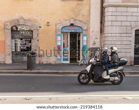 ROME, ITALY - MARCH 29 2014: Young adult man and woman on a scooter in the in the old town on MARCH 29 2014 in Rome in Italy - stock photo